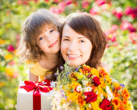 flowers boy: Woman and child with bouquet of flowers against green background. Spring family holiday concept. Mother`s day