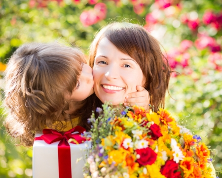 children day: Woman and child with bouquet of flowers against green background. Spring family holiday concept. Mother`s day