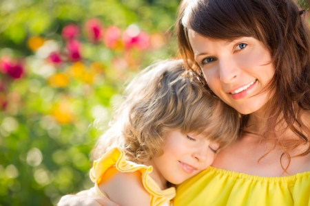 kid's day: Woman and child with bouquet of flowers against green background. Spring family holiday concept. Mother`s day