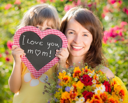 giving: Woman and child with bouquet of flowers against green background. Spring family holiday concept. Mother`s day