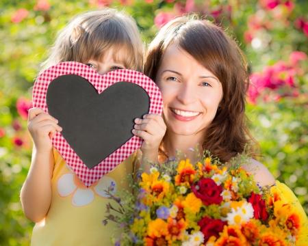 Vrouw en kind met een boeket van bloemen tegen een groene achtergrond. Spring familie concept vakantie. Moeder `s dag