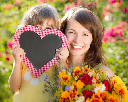 flower bunch: Woman and child with bouquet of flowers against green background. Spring family holiday concept. Mother`s day