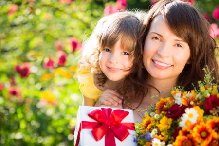 녹색 배경에 꽃의 꽃다발을 가진 여자와 아이. 봄 가족 휴가 개념. 어머니`의 날