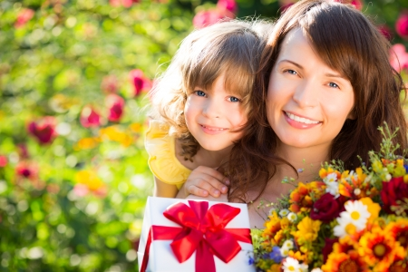 Vrouw en kind met een boeket van bloemen tegen een groene achtergrond. Spring familie concept vakantie. Moeder `s dag Stockfoto - 25083253