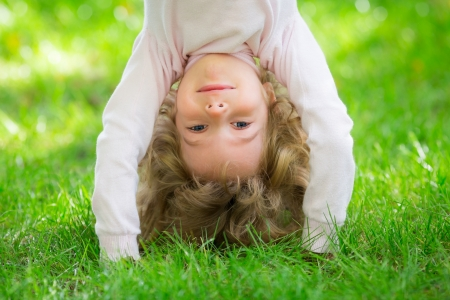 Happy child playing on green grass in spring park photo