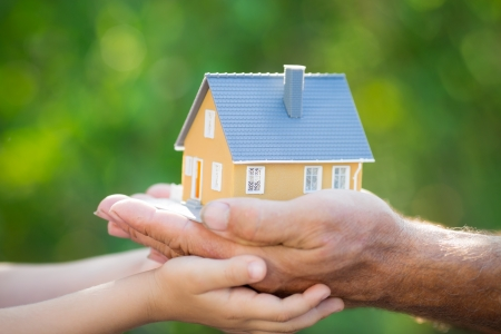 hands holding house: Ecology house in hands against spring blurred background Stock Photo