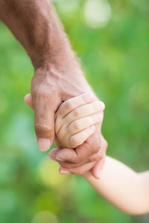 apoyo familiar: Hombre mayor que sostiene al beb� por las manos al aire libre