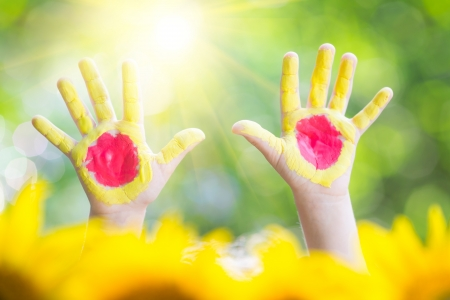 Sunny hands against green spring background photo