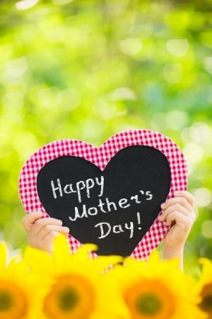 Blackboard blank in heart shape against spring green background photo