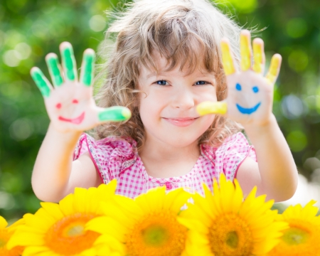 Happy child with smiley on hands against green spring background Stock Photo - 25083211