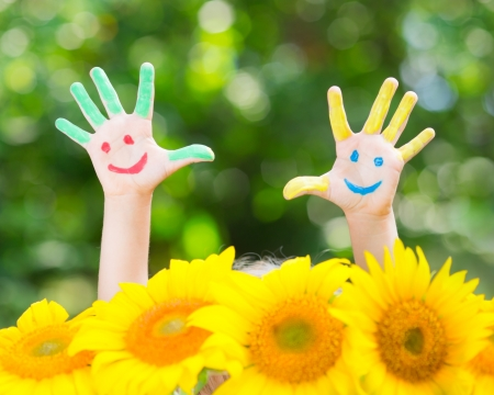 Happy child with smiley on hands against green spring background photo