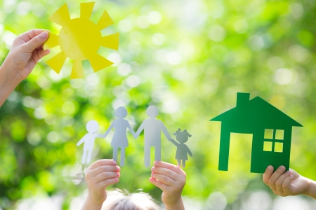 Ecology house and family in hands against spring green background Standard-Bild
