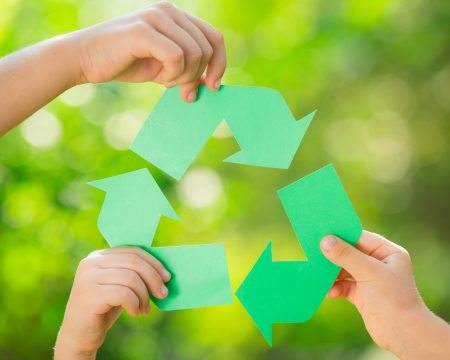 Paper RECYCLE sign in children`s hands against green spring background. Earth day concept Zdjęcie Seryjne