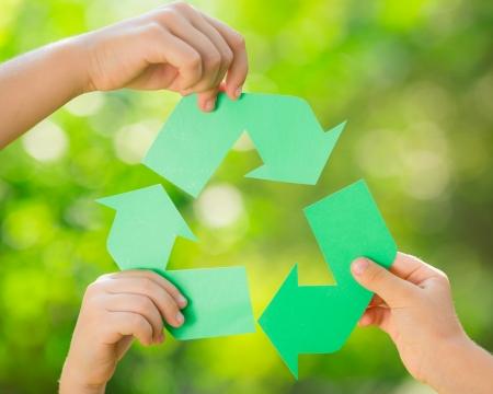 Signo de reciclaje de papel en las manos del `s de los niños contra el fondo verde de la primavera. Concepto del día de la Tierra