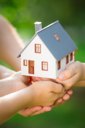 hand holding house: Ecology house in hands against spring blurred background Stock Photo