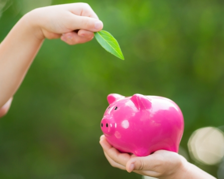 Piggybank and leaf in hands against green spring background photo