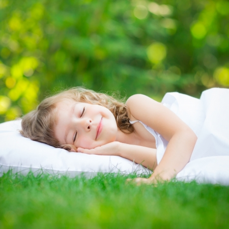 Happy child sleeping on green grass outdoors in spring garden Stock Photo