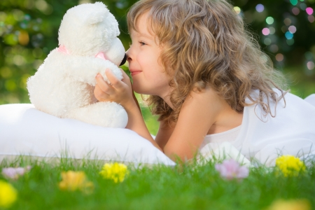 Happy kid with toy teddy bear on green grass outdoors in spring garden photo