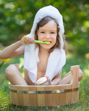 Happy child bathing outdoors on green grass in spring garden Stock Photo - 25222214