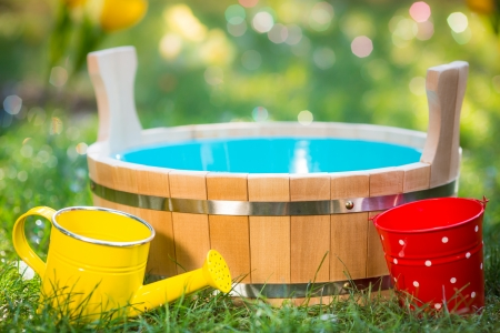 Wooden vat, watering can and bucket on green grass in spring garden photo
