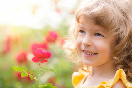Happy child with flower outdoors in spring garden photo