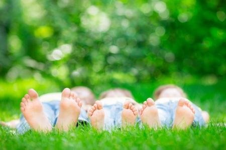 jolie pieds: Famille se trouvant sur l'herbe en plein air dans le parc de printemps
