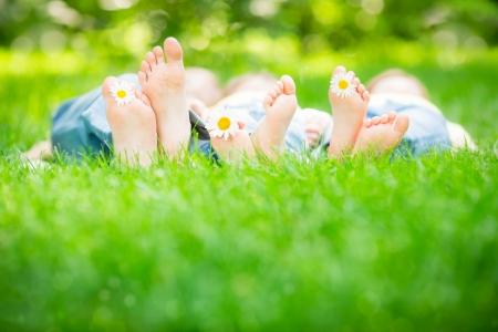 piernas hombre: Familia que miente en hierba al aire libre en el parque de la primavera Foto de archivo