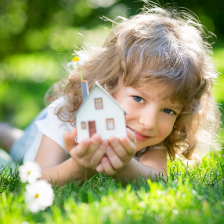 Ecology house in childrens hands against spring green background photo