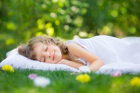 Gelukkig kind slapen op gras buiten in de lente tuin Stockfoto