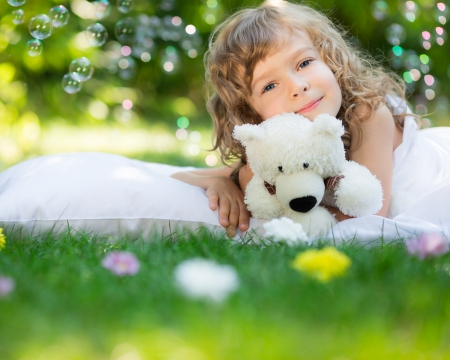 Happy child with toy teddy bear on green grass outdoors in spring garden photo