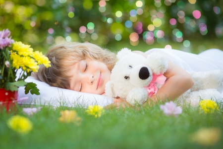 Happy child sleeping with toy teddy bear on green grass outdoors in spring garden photo
