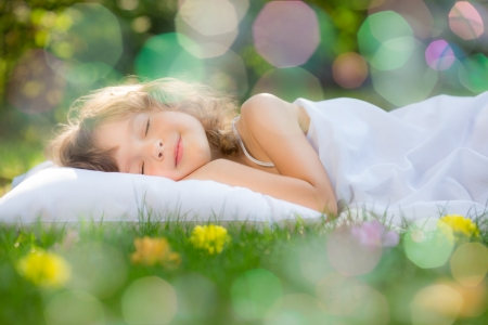 Happy child sleeping on green grass outdoors in spring garden photo