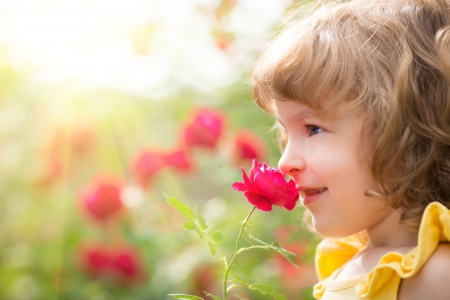 Happy child with flower outdoors in spring garden