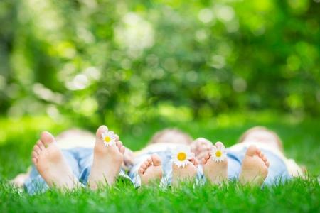 春の公園で、屋外の芝生の上に横たわる家族