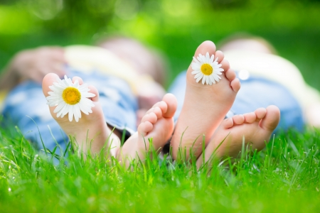 pied jeune fille: Couple couch� sur l'herbe en plein air dans le parc de printemps