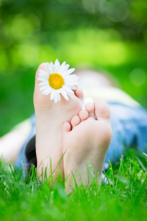 Kid lying on grass outdoors in spring park photo