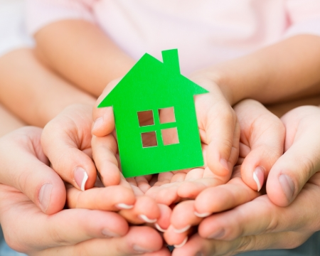 Family holding green paper house in hands. Real estate concept photo