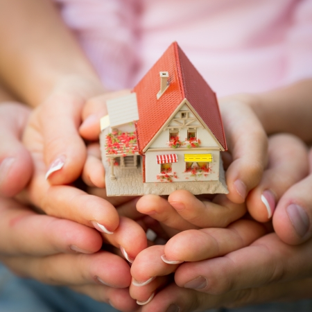 Family holding little house in hands. Real estate concept photo