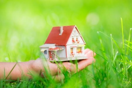 Little house in children`s hand against green spring background. Shallow depth of field photo