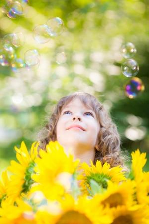 burbujas de jabon: Niño feliz con el girasol al aire libre en el parque de la primavera Foto de archivo