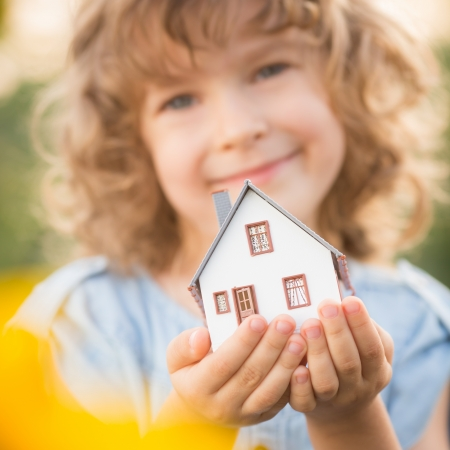 home protection: Child holding house in hands against sunflower field background. Real estate concept
