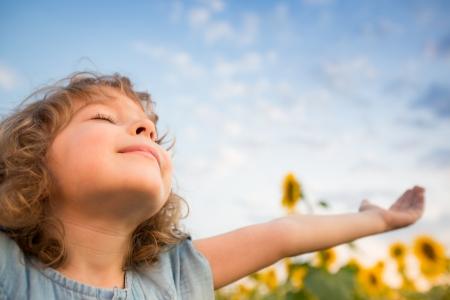 manos levantadas al cielo: Infantil al aire libre felices en campo de girasol de primavera Foto de archivo