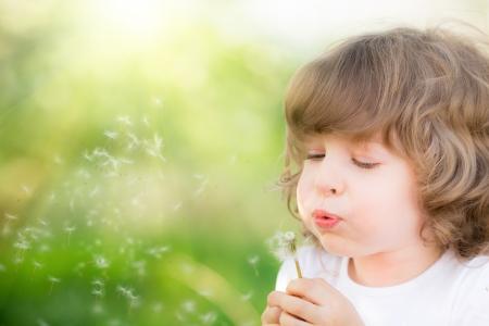 blowing dandelion: Il bambino felice che soffia il dente di leone all'aperto nel parco di primavera