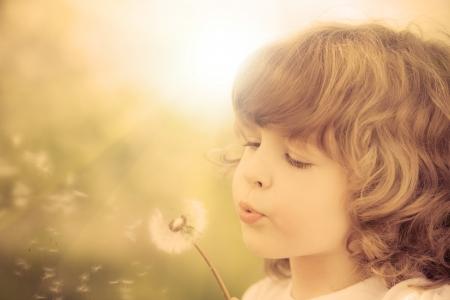 Niño feliz que sopla el diente de león al aire libre en el parque de la primavera