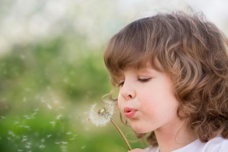 Gelukkig kind blaast paardebloem buiten in het voorjaar van park