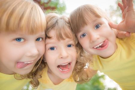 niños jugando: Inusual ángulo de visión baja retrato de niños felices jugando al aire libre en el parque de la primavera. Tiro de ojo de pez