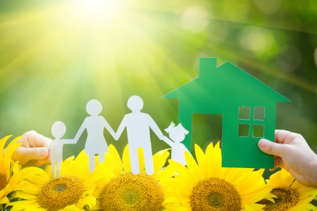 yellow house: Children holding paper house and family in hands outdoors Stock Photo