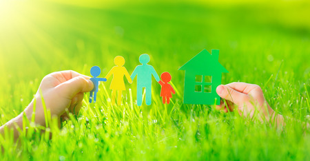 multi family house: Paper house and family in hands over spring green grass. Ecology concept