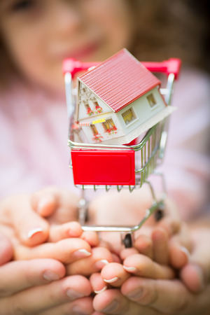 Familia que sostiene la casa pequeña en el carro de compras Profundidad del campo baja