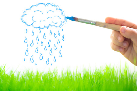 Drawing clouds and rain over spring green grass photo